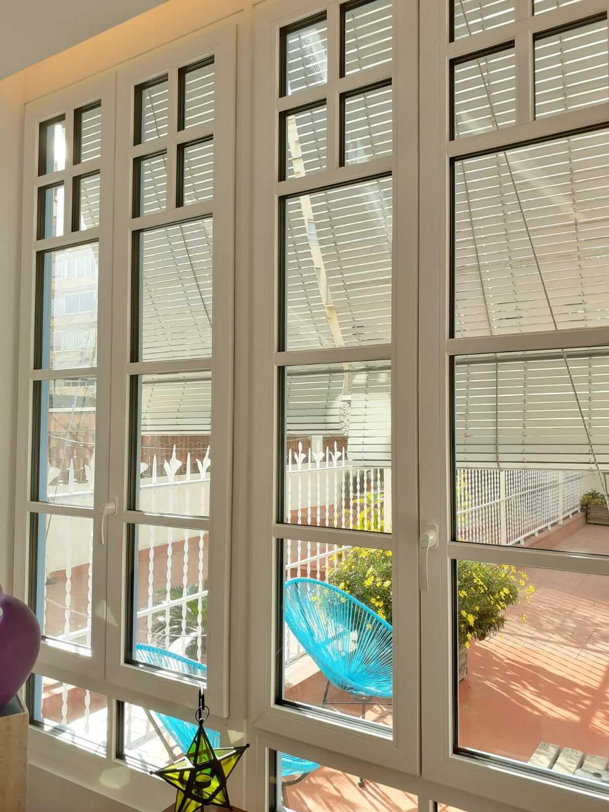 Ventana de PVC color blanco con barrotillo inglés instalada en Barcelona